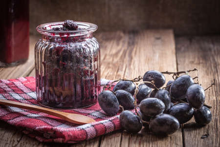 Dark grape jam on a wooden table. Imagens