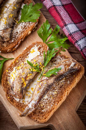 sardine can: Sandwich with sprats with parsley and lemon.