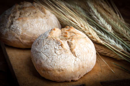 crusty: Freshly baked crusty rolls on old rustic wooden boards. Stock Photo