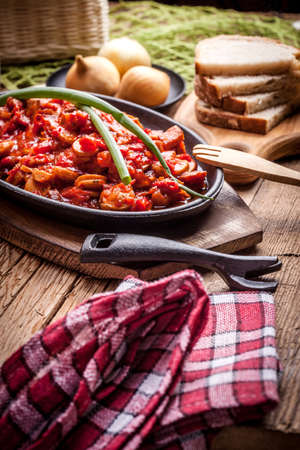 cast iron red: Lecho - Delicious Hungarian dish in cast iron pan.