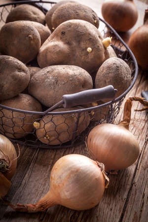 organically: Organically grown potatoes in a metal basket on a wooden table.
