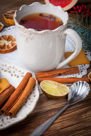 apple and orange: Hot tea with citrus, cinnamon, cloves and honey on a wooden table.