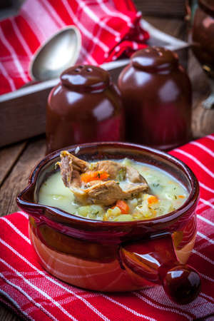 Cucmber soup with ingredients on a wooden table.