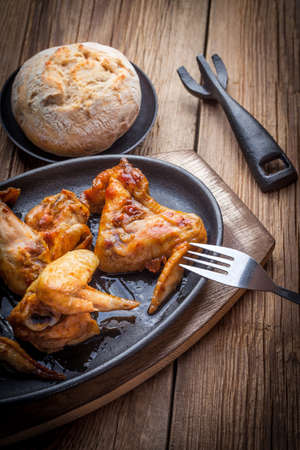 Cast iron frying pan with roasted chicken wings. Selective focus.