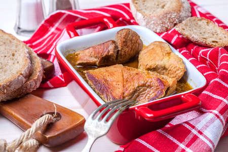 Braised pork in gravy with fresh bread on a wooden table.