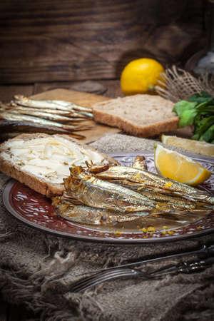 sprats: Tasty smoked sprats on plate. Stock Photo