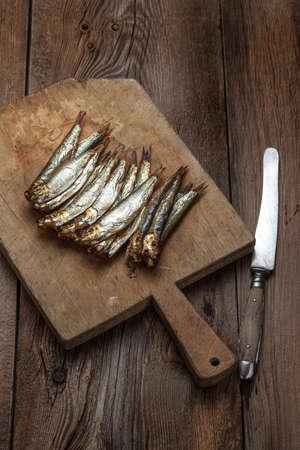 sprats: Tasty smoked sprats on a chopping board.