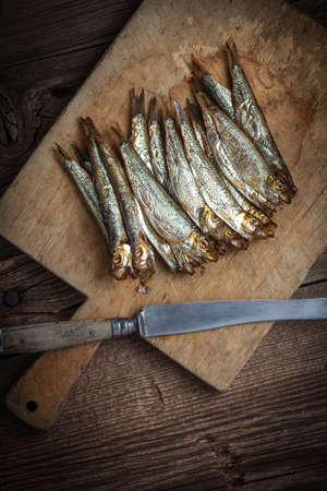 sprats: Tasty smoked sprats on a chopping board.