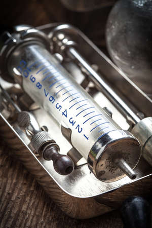 cupping glass cupping: Retro syringe, stethoscope and medical cupping glass on a wooden table.