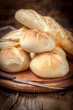 kaiser: Several kaiser rolls and baquette on a wooden table. Stock Photo