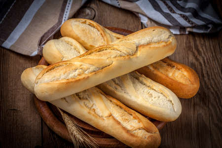 life loaf: French baguettes on old wooden table. Selective focus. Stock Photo
