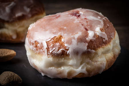 dough nut: Donut with icing and rose jam. Dark light. Stock Photo