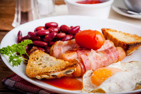 english breakfast: Full English breakfast with bacon, sausage, fried egg and baked beans.