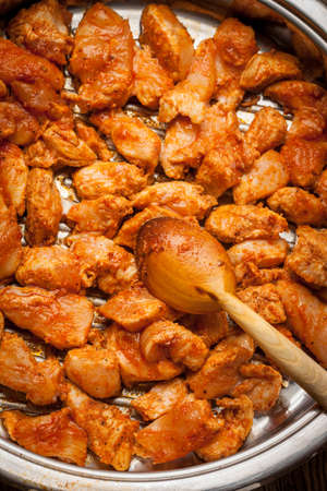 Pieces of fried chicken with spices in a pan. Selective focus. Stock Photo