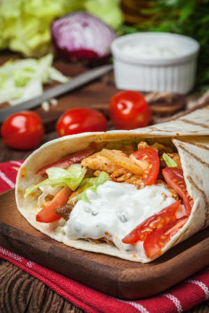 vetical: Tasty fresh wrap sandwich with chicken, vegetables and tzatziki sauce. Stock Photo
