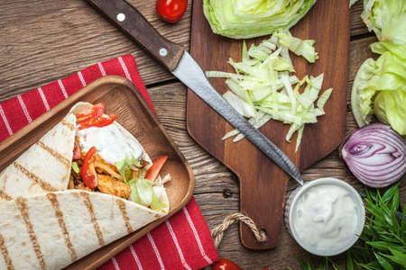 tzatziki: Tasty fresh wrap sandwich with chicken, vegetables and tzatziki sauce. Stock Photo