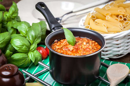 bolognese sauce: Pasta, bolognese sauce and basil on wooden table.