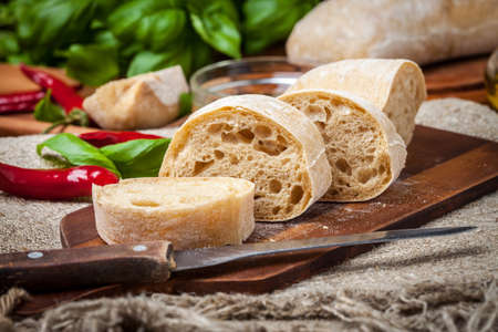 ciabatta: Sliced ciabatta bread on cutting board. Selective focus.