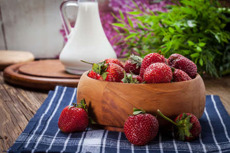 full filled: Bunch of ripe strawberries in a wooden bowl on the table.