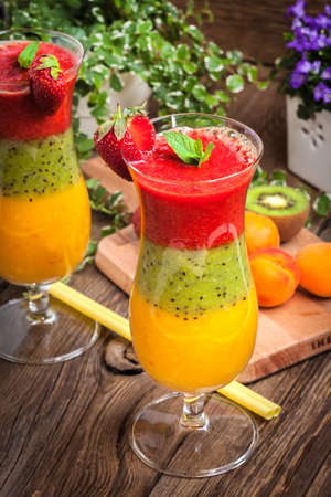 trichromatic: Smoothies with fresh fruit. Strawberries, apricots, kiwi. Selective focus.