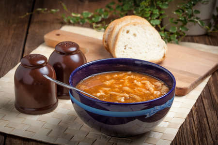 tripe: Traditional polish tripe soup with vegetables in blue bowl.