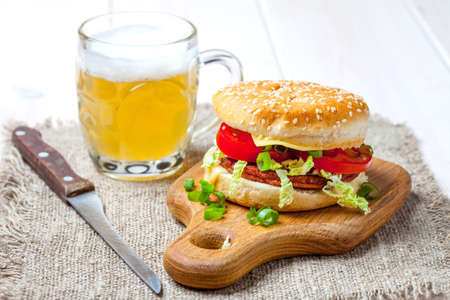 Homemade hamburger with fresh vegetables on wooden board.