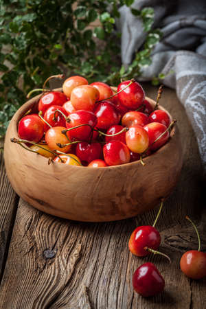 pulpy: Freshly harvested cherries in a wooden bowl. Dark light. Stock Photo