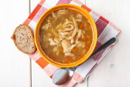Traditional polish tripe soup with vegetables in orange bowl. Top view. Stock Photo