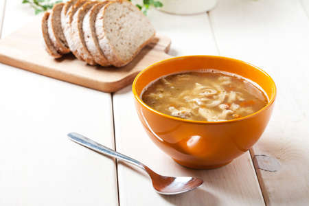 tripe: Traditional polish tripe soup with vegetables in orange bowl. Stock Photo