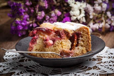 icing sugar: Piece of homemade fresh plum cake with icing sugar.