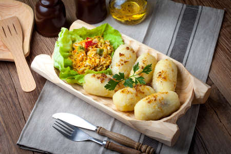Potato dumplings stuffed with minced meat in a wooden bowl.