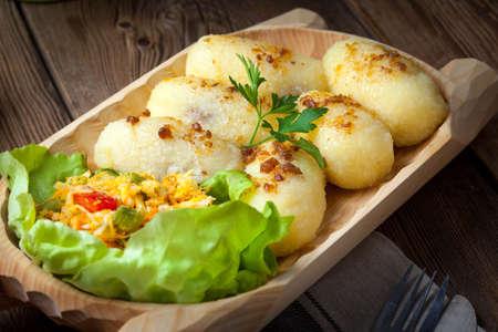 Potato dumplings stuffed with minced meat in a wooden bowl.
