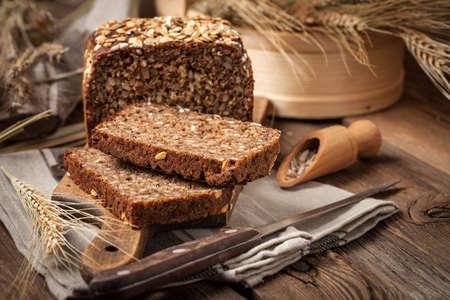 Todo el pan de centeno de grano con las semillas en una tabla de madera. Foto de archivo