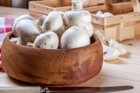 Mushrooms in a bowl on a wooden table.