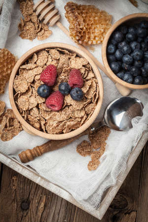 Healthy breakfast - bowl of cereals with blueberries and raspberries on a wooden table.