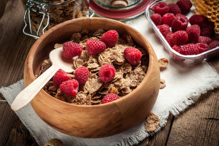 Healthy breakfast - bowl of cereals with raspberries on a wooden table. Stock Photo