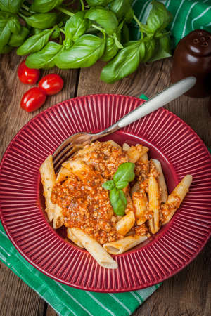 Penne a bolognese on red plate. Shallow depth of field.