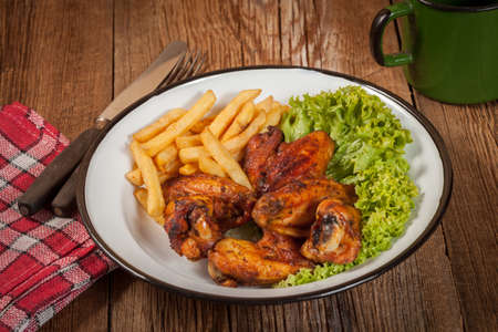 Roasted chicken wings and chips. Selective focus.
