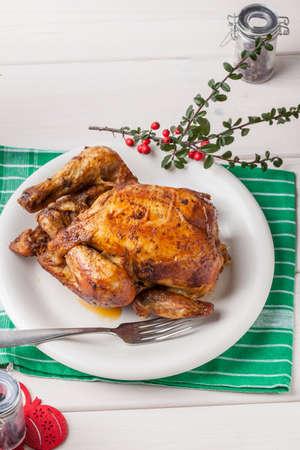 Baked chicken for Christmas dinner on white plate.