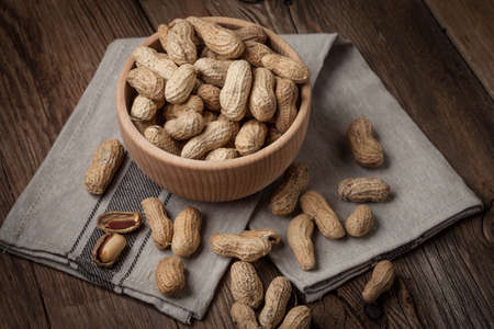 Dried peanuts in wooden bowl. Selective focus.