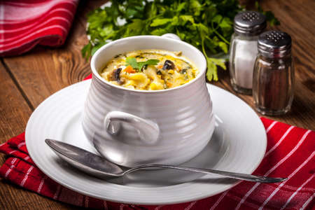 Tasty mushroom soup with noodles farfalline on a wooden table. Shallow depth of field.