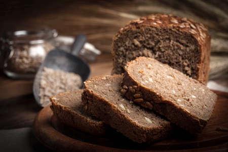 Wholemeal bread with sunflower seeds. Dark light.