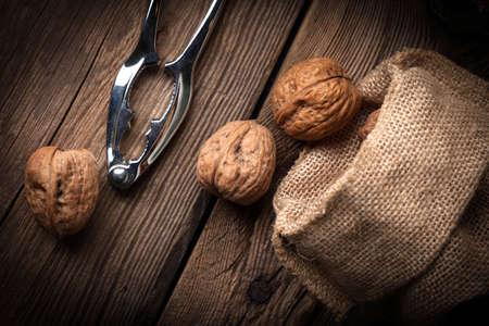 Walnuts in burlap bag on old wood table. Dark light.