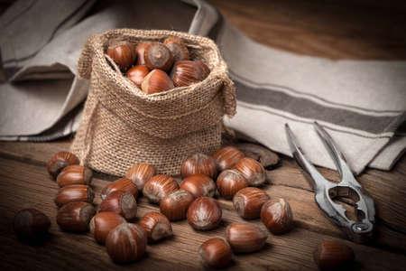 Hazelnut in burlap bag on old wood table. Dark light. Stock Photo