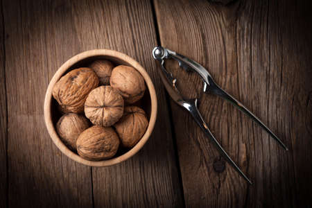 Walnuts in wooden bowl on old wood table. Dark light. Top view. Stock Photo