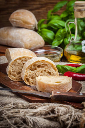 Sliced ciabatta bread on cutting board. Selective focus.