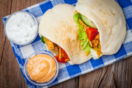 Fried chicken meat with vegetables in pita bread. Selective focus.