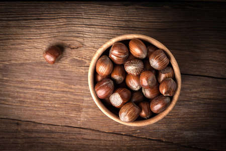 Hazelnuts in wooden bowl on old wood table. Dark light.