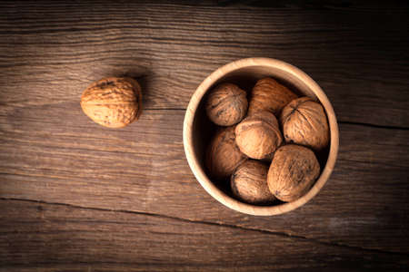 Walnuts in wooden bowl on old wood table. Dark light. Stock Photo