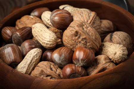 Walnuts, hazelnuts and peanuts in wooden bowl on old wood table. Dark light.